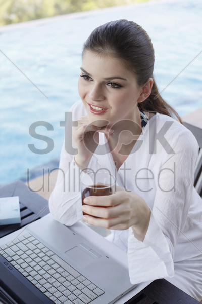 woman with a glass of tea contemplating stock photo