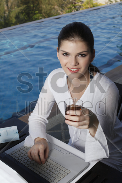 woman with a glass of tea using laptop stock photo