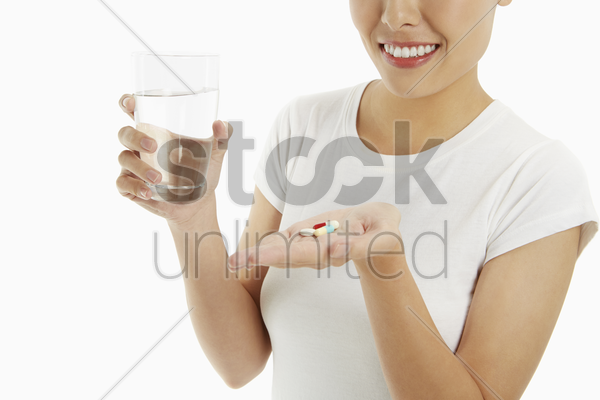 woman with a glass of water and pills stock photo