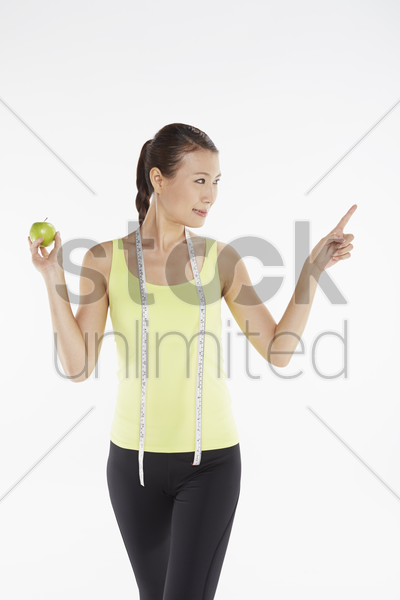 woman with a green apple and measuring tape stock photo