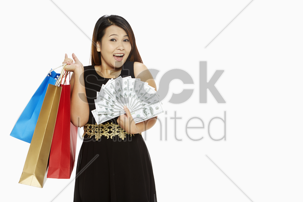 woman with a lot of money carrying paper bags stock photo