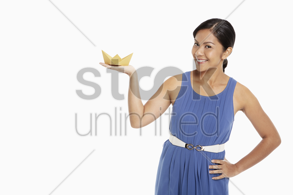 woman with a paper boat on her palm stock photo