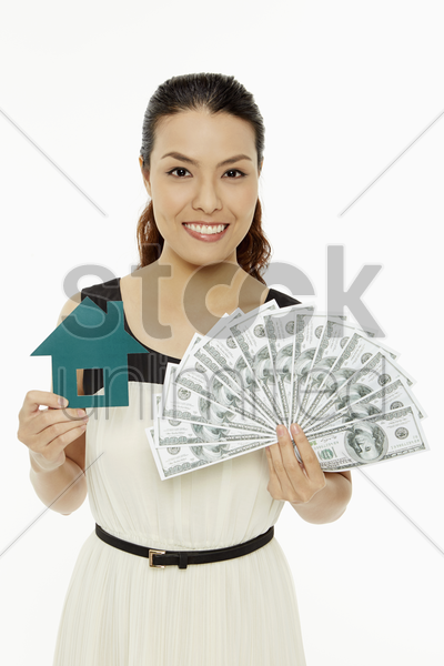 woman with a paper house and cash stock photo