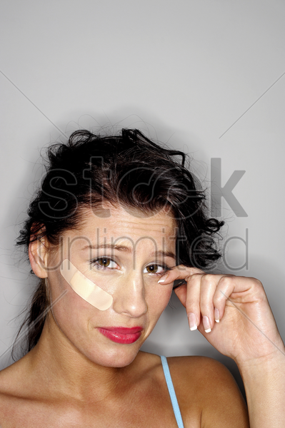 woman with a plaster on her face crying stock photo