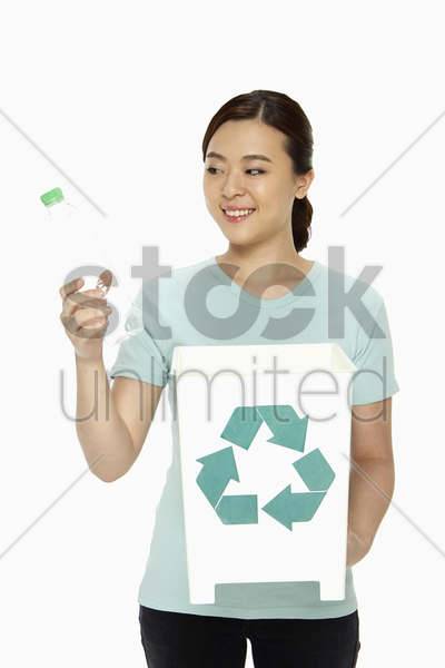 woman with a plastic bottle and a recycling bin stock photo