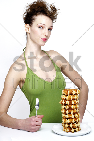 woman with a plate of stacked up doughnuts stock photo