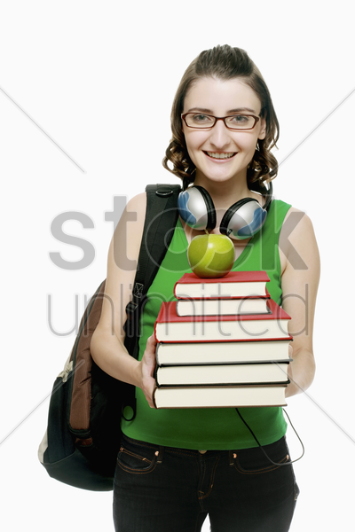 woman with a stack of books and a green apple stock photo