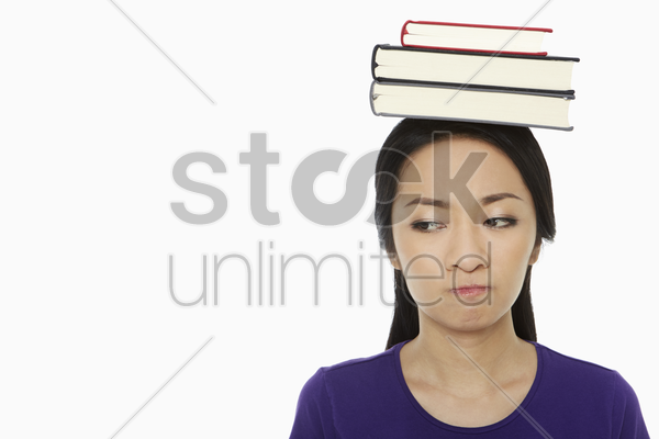 woman with a stack of books on her head, sulking stock photo