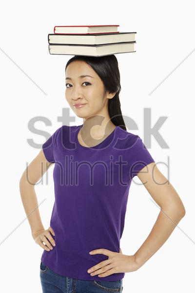 woman with a stack of books on her head stock photo