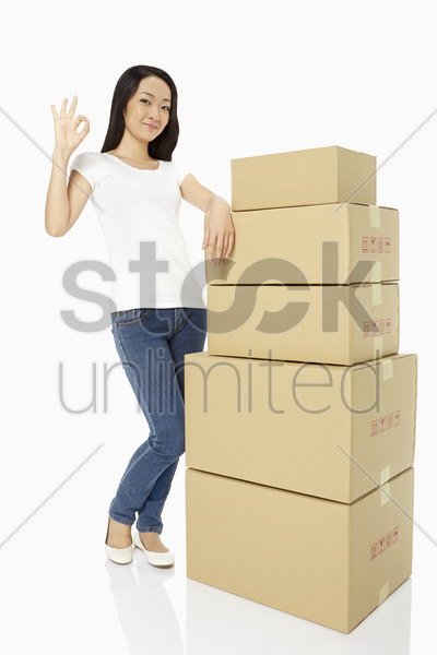 woman with a stack of gift boxes, showing hand gesture stock photo