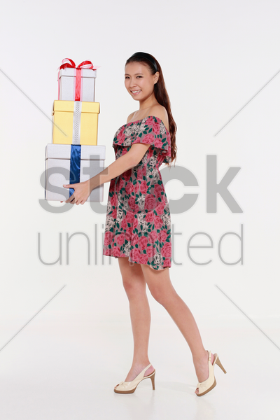 woman with a stack of gift boxes stock photo