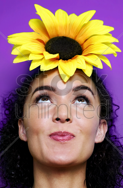 woman with a sunflower on top of her head stock photo