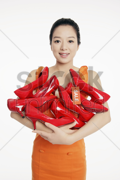 woman with an armful of shoes stock photo