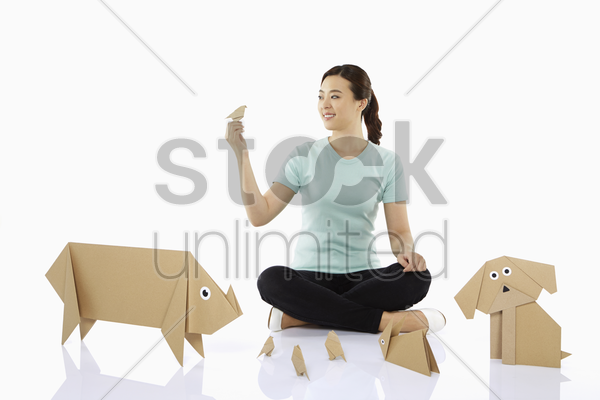 woman with an assortment of paper animals stock photo
