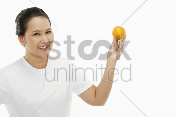 woman with an orange fruit stock photo