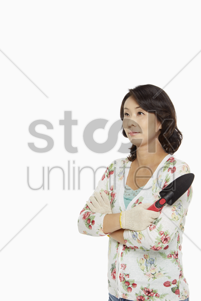 woman with arms crossed holding a spade stock photo