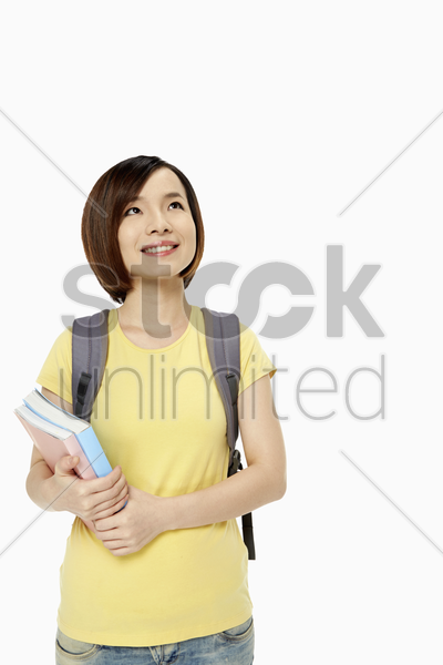 woman with backpack and books smiling stock photo