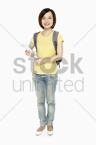 woman with backpack carrying books stock photo