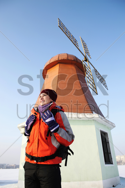 woman with backpack walking during winter time stock photo