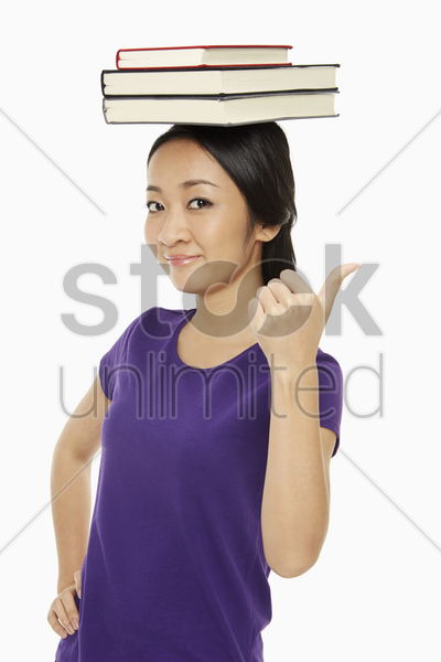 woman with books on her head showing hand gesture stock photo
