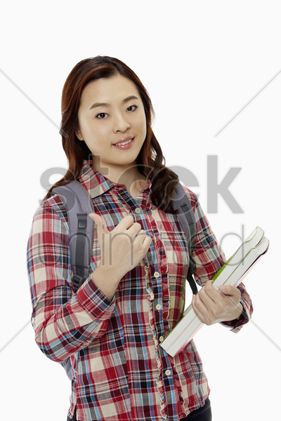 woman with books showing hand gesture stock photo