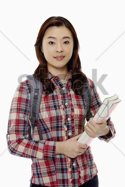 woman with books smiling at the camera stock photo
