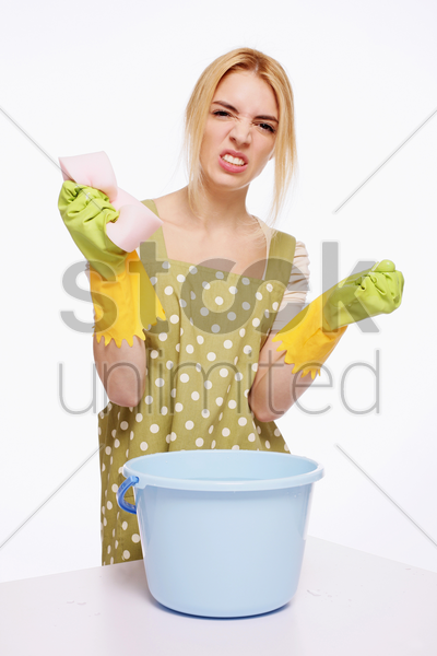 woman with cleaning sponge looking frustrated stock photo