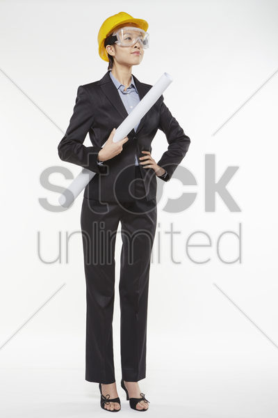 woman with construction helmet and safety glasses holding a roll of paper stock photo