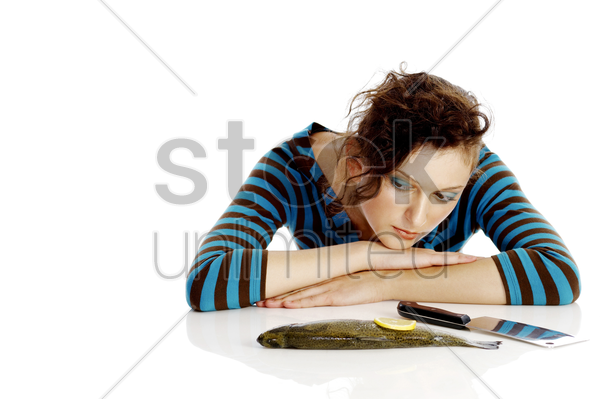 woman with fish and knife on the table stock photo