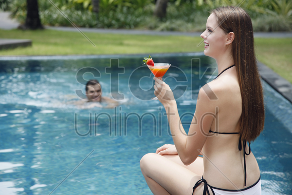 woman with glass of cocktail sitting by the pool side, man swimming towards woman stock photo