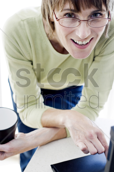 woman with glasses holding a cup while using laptop stock photo