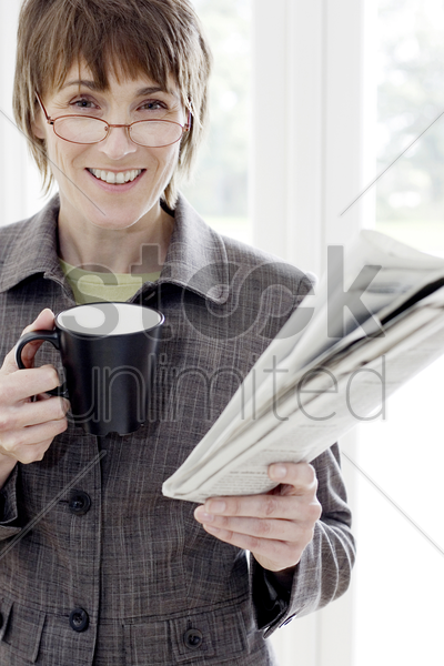 woman with glasses holding cup and newspaper stock photo