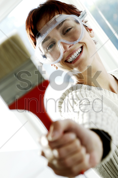 woman with goggles holding a paintbrush stock photo