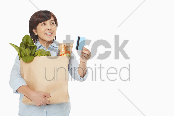 woman with groceries holding up a credit card stock photo