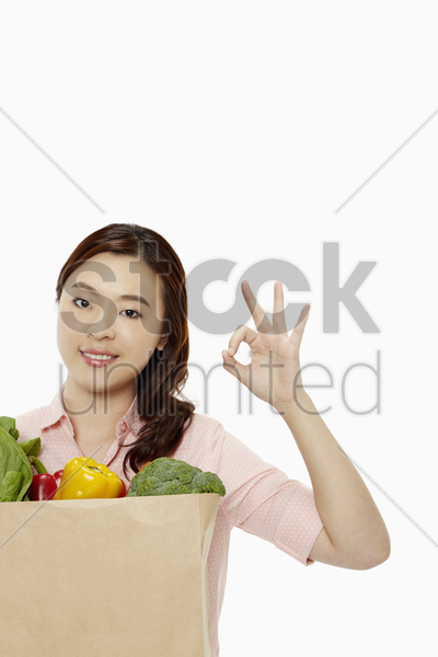 woman with groceries showing hand gesture stock photo