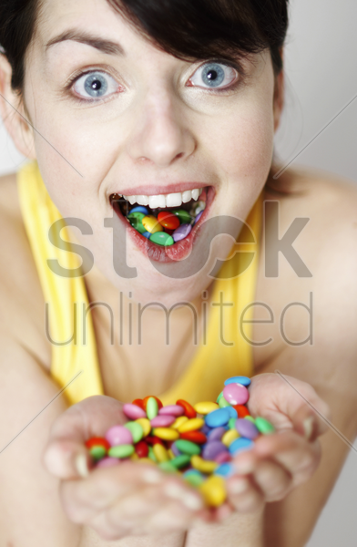 woman with handful and mouthful of candies stock photo