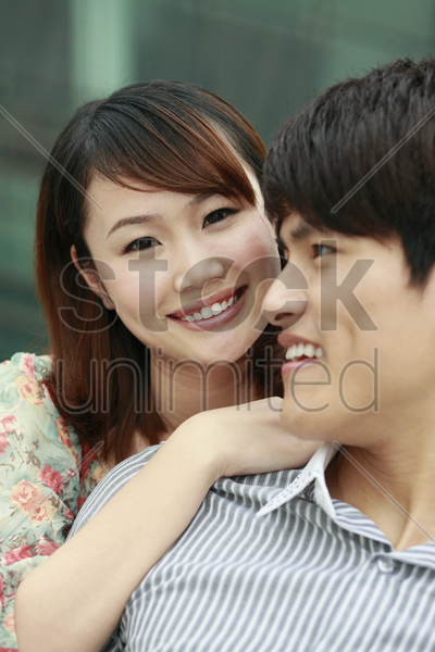 woman with hands around man's neck stock photo