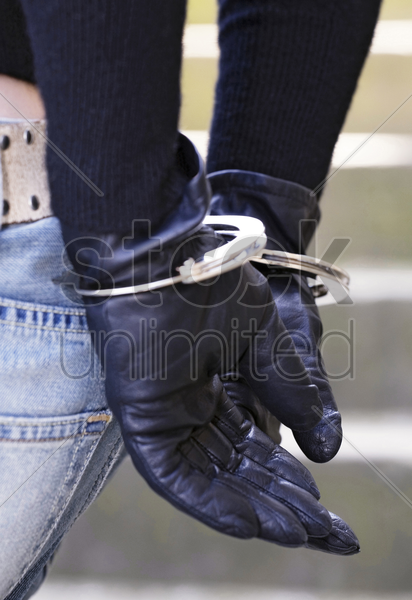 woman with her hands handcuffed to the back stock photo