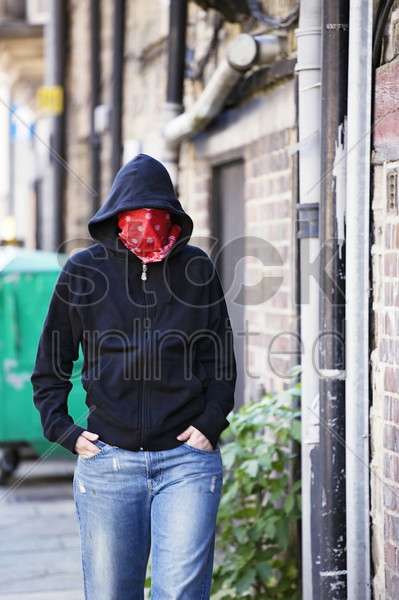woman with hooded jacket and scarf covering her face stock photo