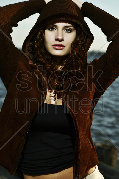 woman with hooded jacket looking at the camera stock photo