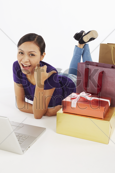 woman with laptop and shopping items stock photo