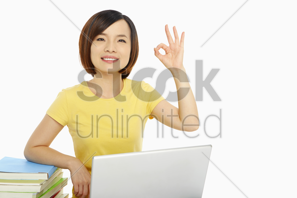 woman with laptop showing hand gesture stock photo