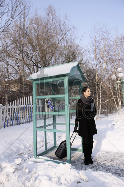 woman with luggage standing at the telephone booth stock photo
