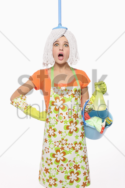 woman with mop on her head carrying a pail of cleaning products stock photo