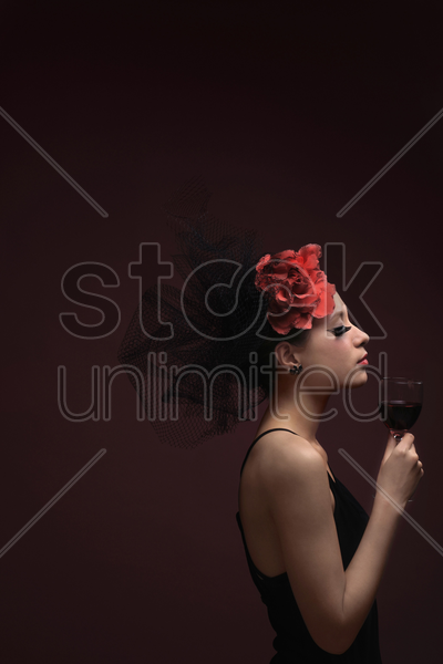 woman with net and flower decorating her hair holding wine glass stock photo