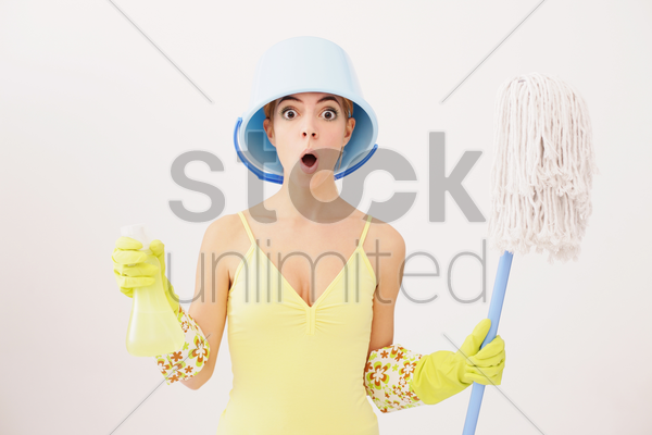 woman with pail on head holding mop and spray bottle stock photo