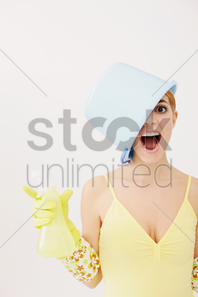 woman with pail on head shouting while holding spray bottle stock photo
