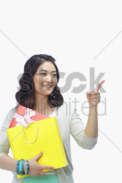 woman with paper bag pointing to the left stock photo
