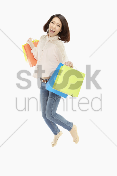 woman with paper bags, jumping mid air stock photo