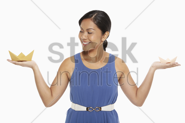 woman with paper boats on both palms stock photo